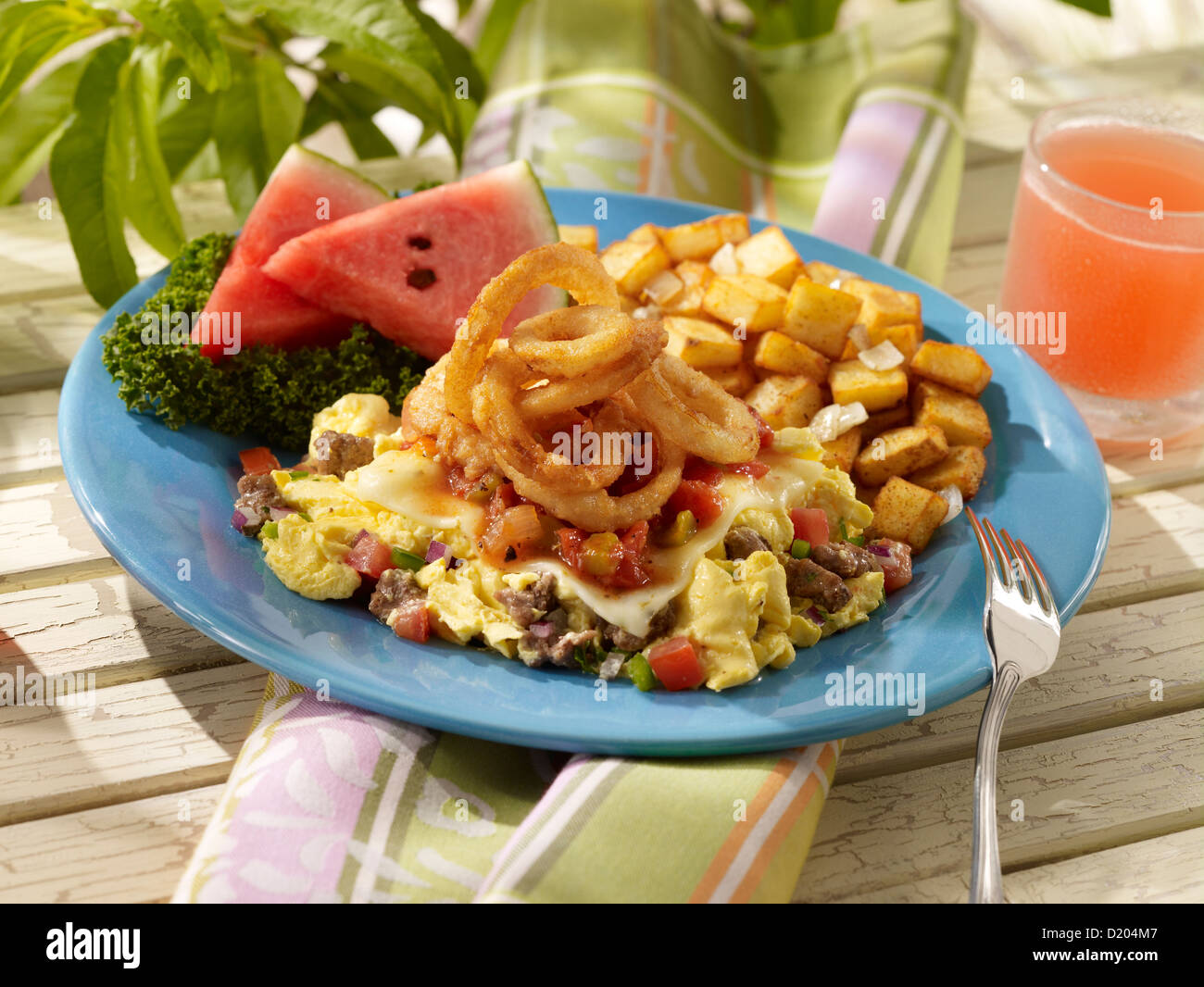 Santa Fe summer scramble topped with onion rings and served with potatoes - Stock Image