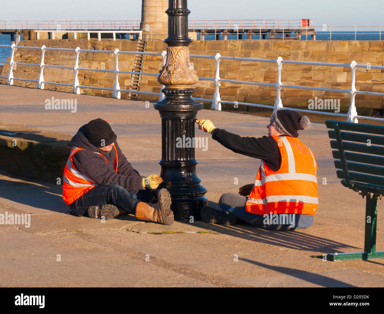 Two offenders on the Community Payback scheme, administered by the Probation Service, painting a lamppost on Whitby - Stock Image