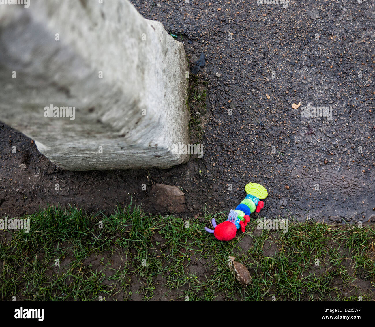 A baby's toy (worm-shaped teething ring or aid) is dropped on the muddy ground - Stock Image