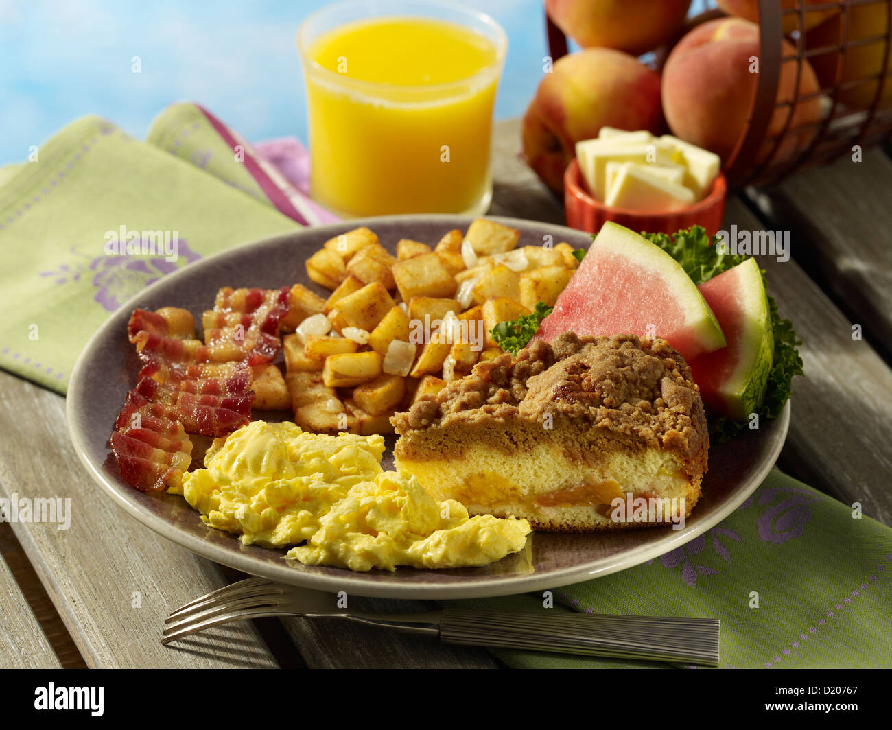 Scrambled eggs and bacon with peach coffee cake, potatoes and fruit - Stock Image