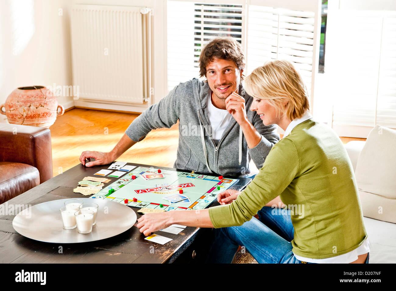 Young couple playing monopoly, Hamburg, Germany - Stock Image