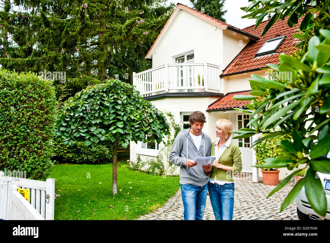 Young couple is looking at documents in front of a house, Hamburg, Germany - Stock Image