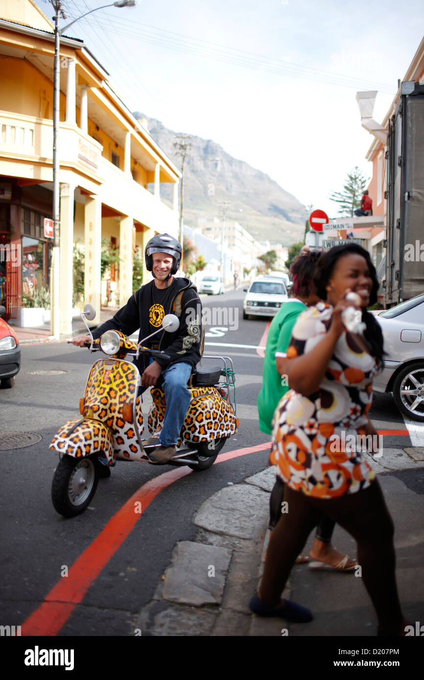 Man on leopard print scooter cruising through Observatory, Southern Suburbs, Cape Town, South Africa, Africa - Stock Image