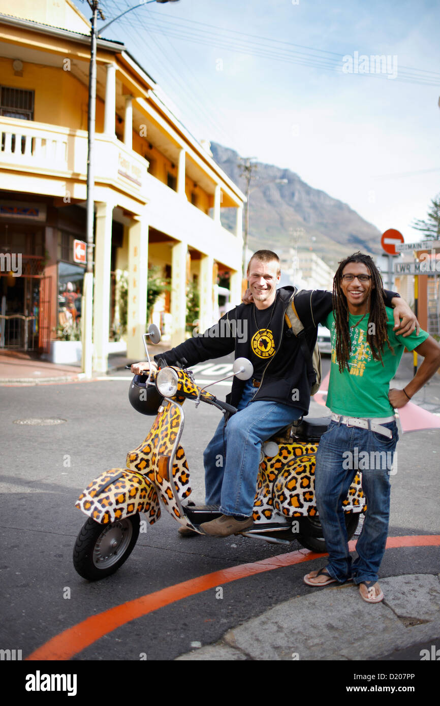 Two men on leopard print scooter cruising through Observatory, Southern Suburbs, Cape Town, South Africa, Africa - Stock Image