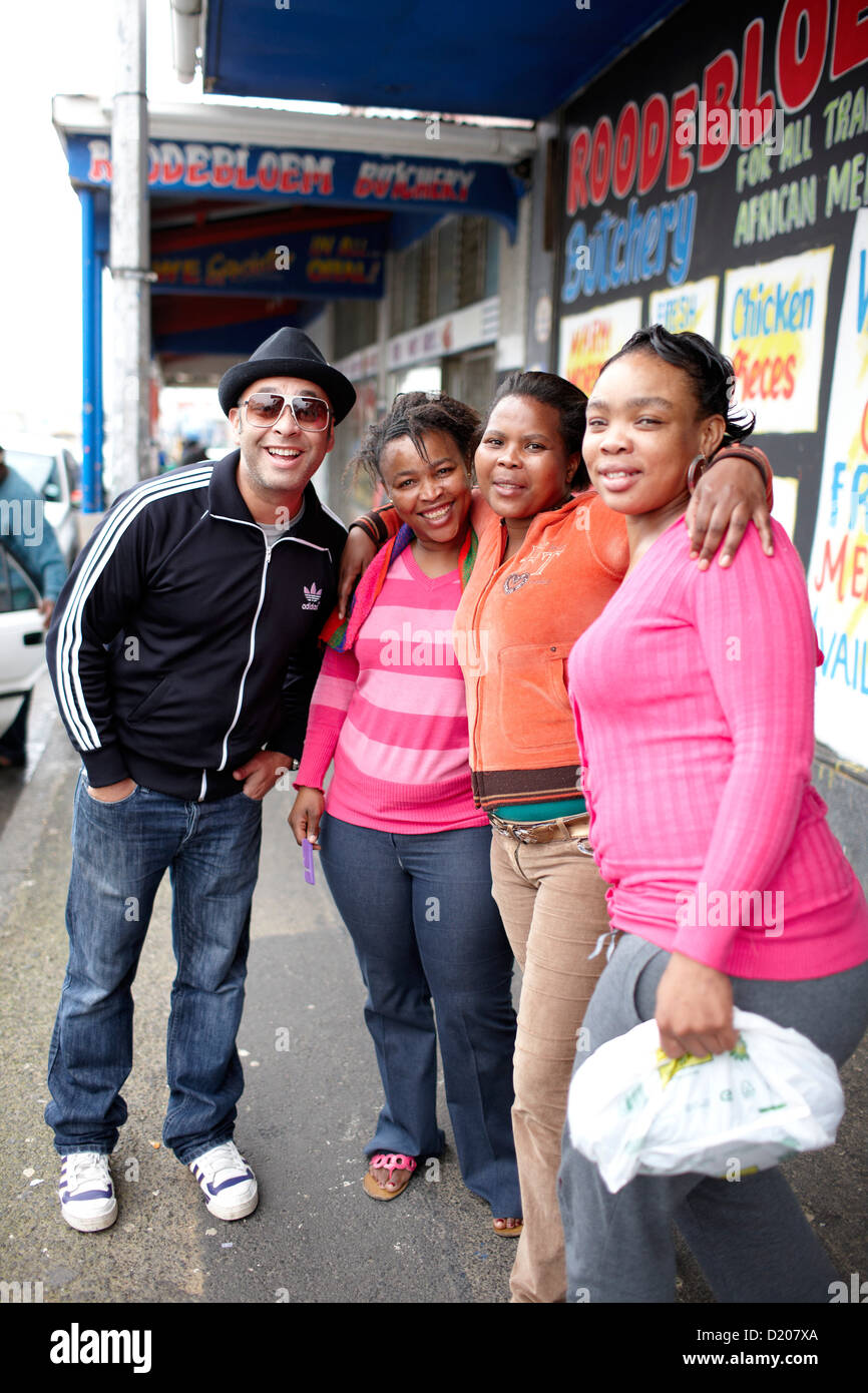 Comedian Kurt Schoonrad striking a pose with three women, Cape Town, South Africa, Africa - Stock Image