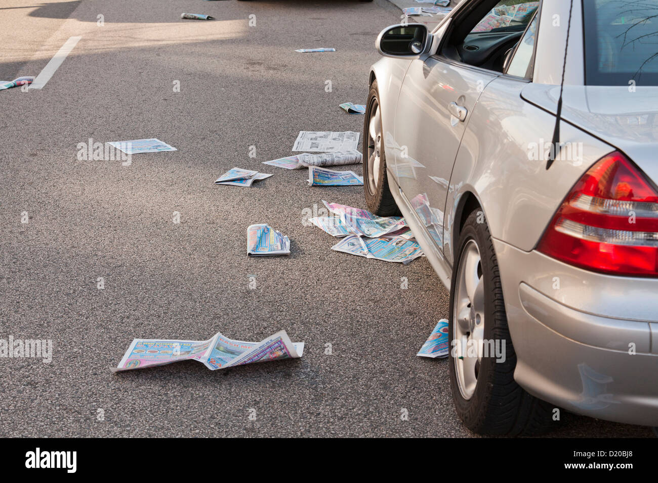 Newspapers littered on street - USA - Stock Image