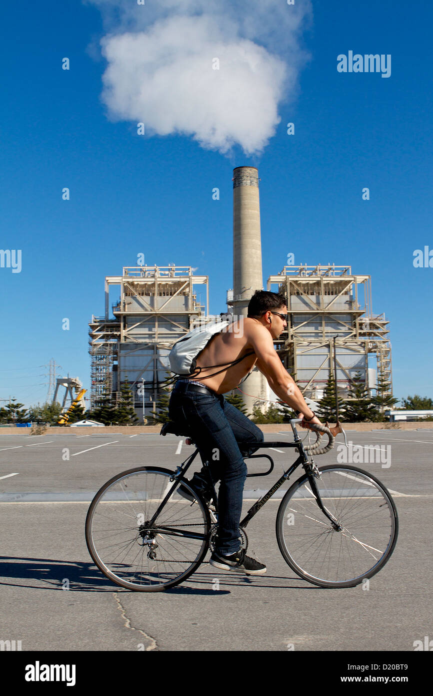 AES Huntington Beach Generating power Station, with a cyclist exercising in the foreground - Stock Image