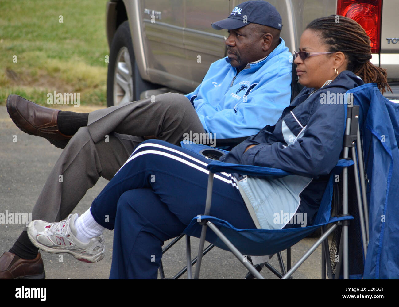 Couple watching a high school,tennis match from the parking lot - Stock Image