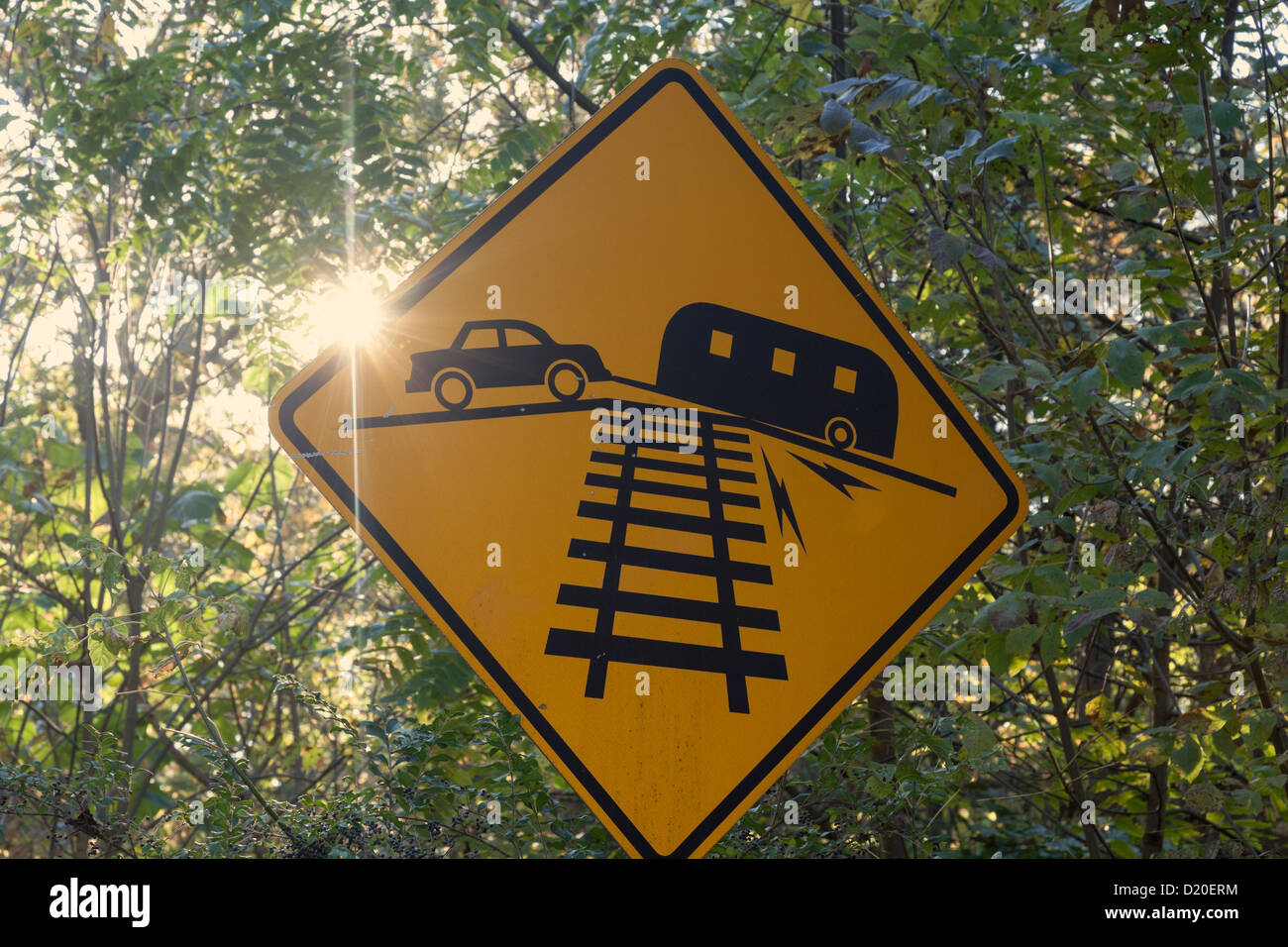 Car pulling small RV - yellow sign and the sun ray - Stock Image