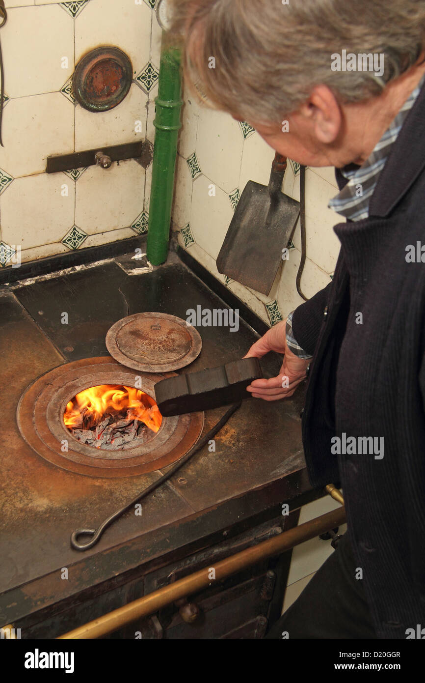 A man puts a briquette in an old stove - Stock Image