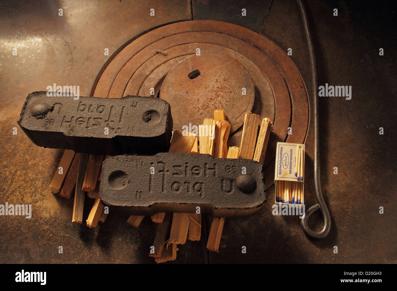 Two Briquettes and some wood on an old stove - Stock Image