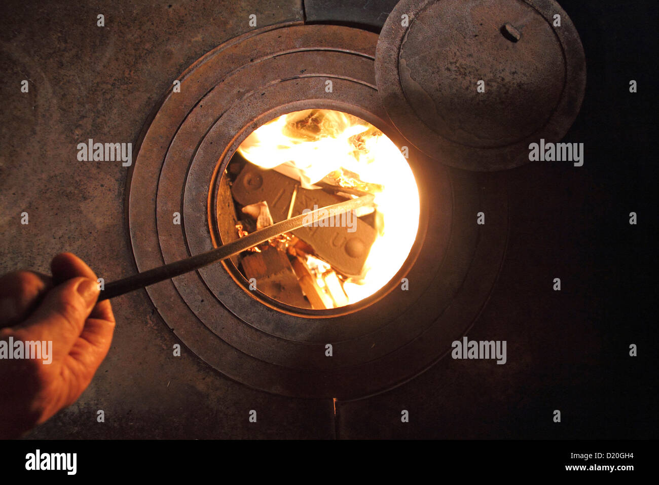A man puts a log of wood in an old stove - Stock Image