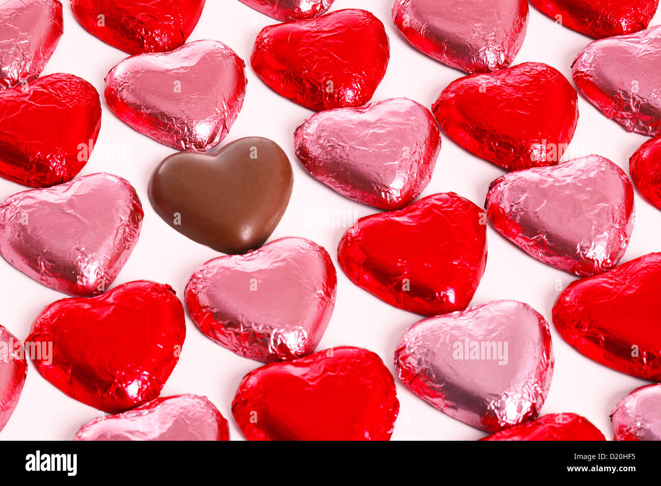 Chocolate hearts in red and pick foil wrappers on a white background, with one unwrapped heart in amongst the group. - Stock Image