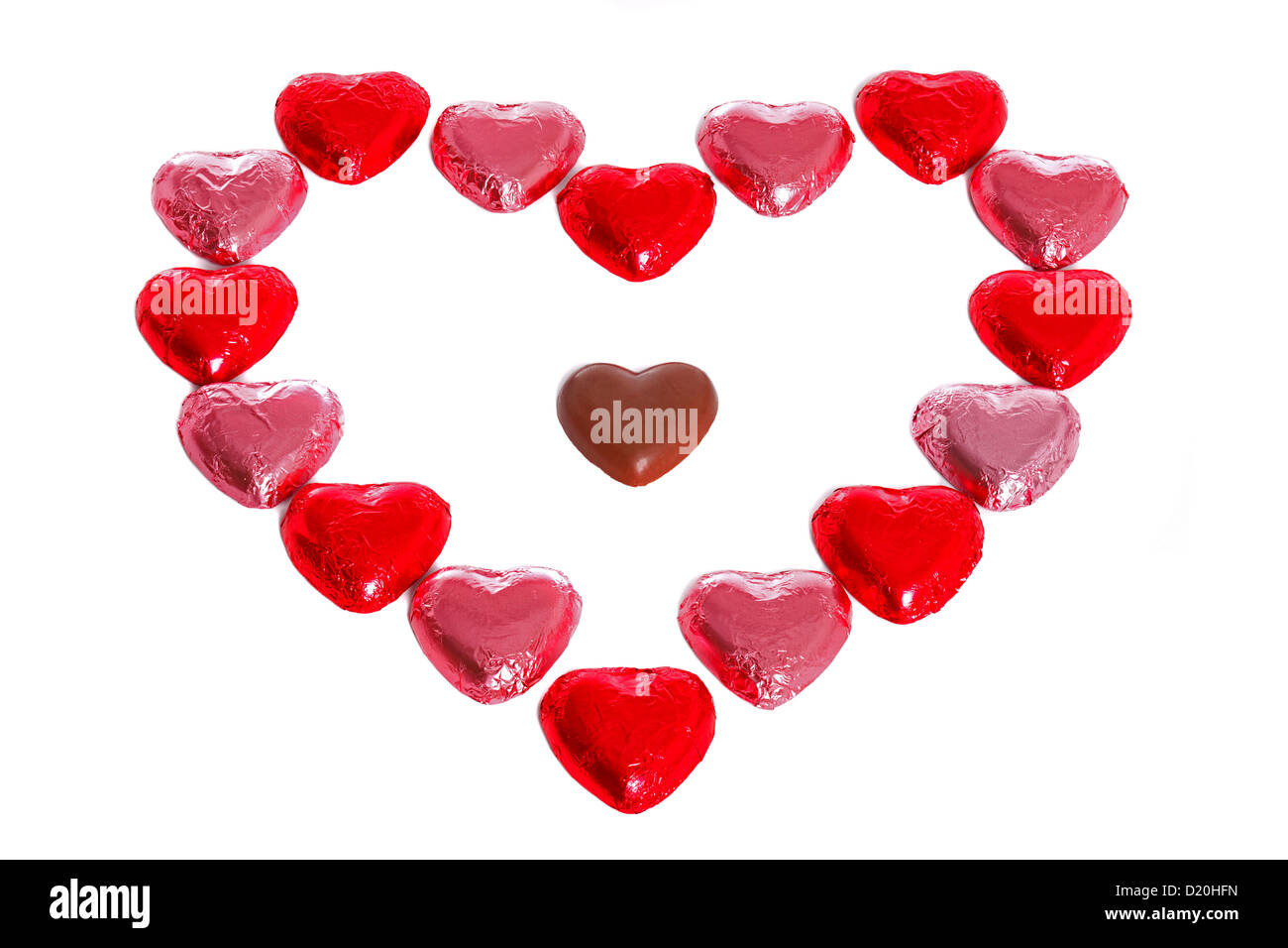 A heart made out of foil wrapped chocolates with an unwrapped one in the middle, white background. - Stock Image