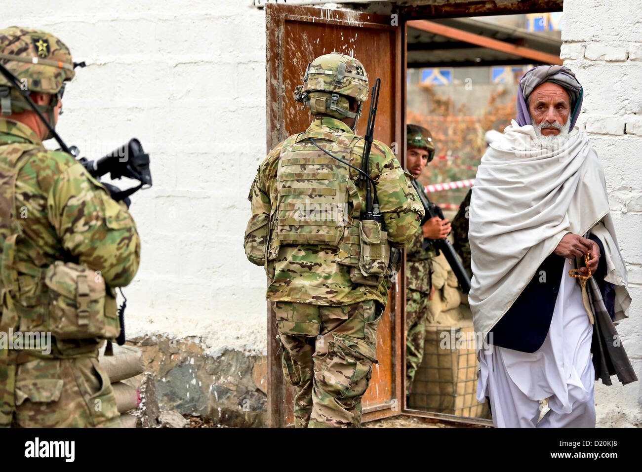 US Army forces pass an Afghan man during a patrol January 8, 2013 in Farah City, Afghanistan. - Stock Image