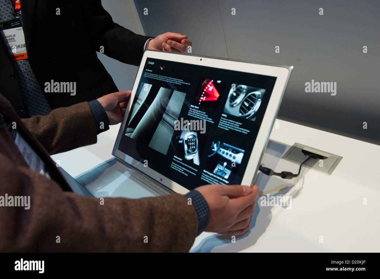 Las Vegas, US - 2013-01-08. A CES attendee lifts Panasonic's 20' 4k tablet with a Panasonic representative - Stock Image