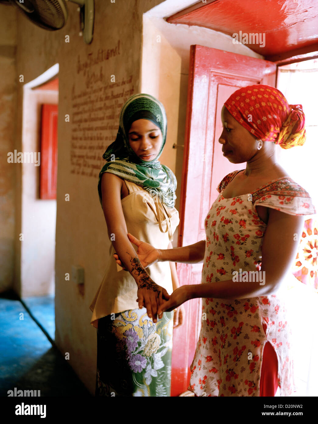 Therapist Acha with client shows henna painting at Mrembo Spa, Mrembo means beautiful woman, old house in the center - Stock Image