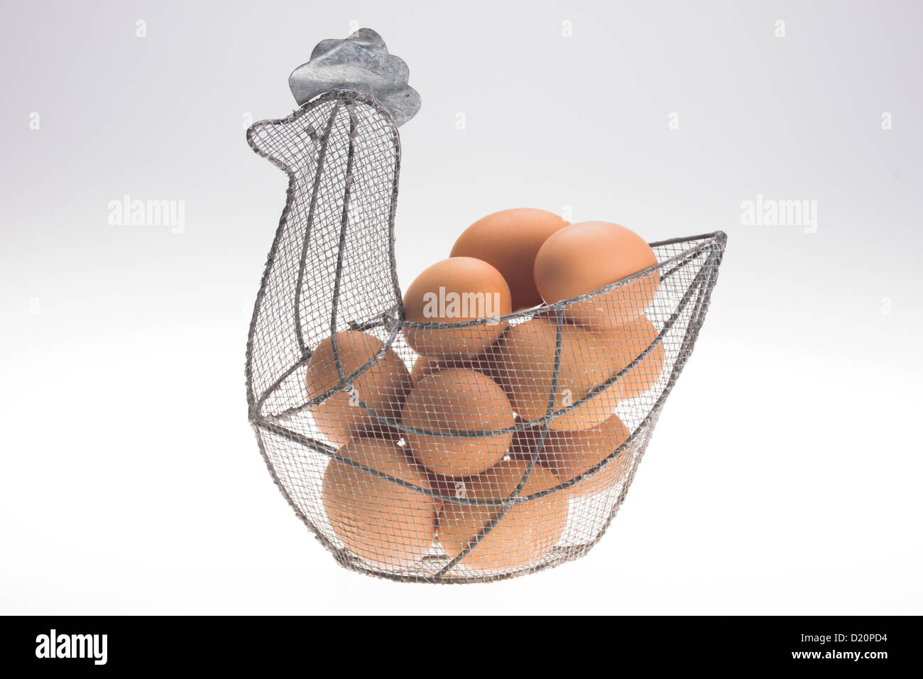 Home-produced eggs from garden hens in a wire storage basket shaped like a chicken. - Stock Image