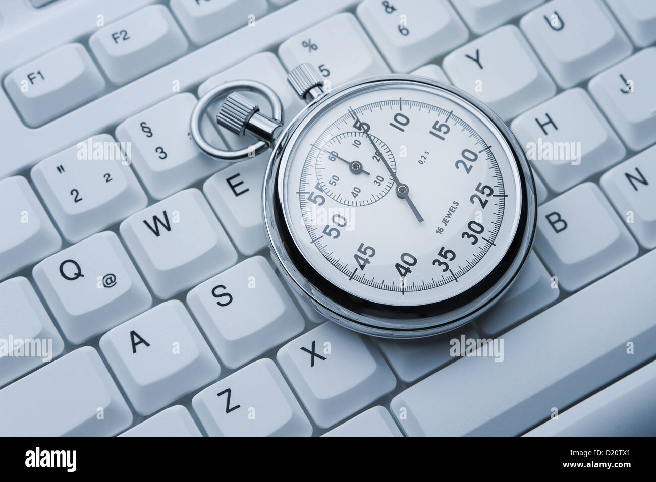 Close up of silver stopwatch lying on the keyboard - Stock Image