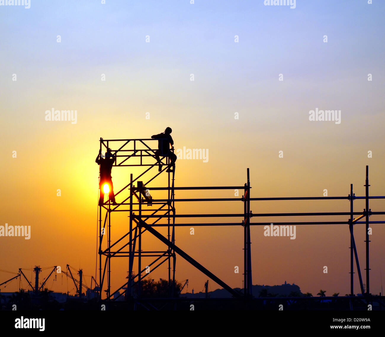 Construction workers high up on a scaffold seen against the setting sun - Stock Image