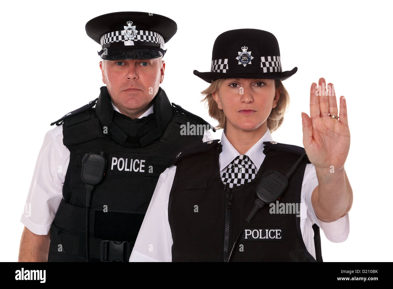 Studio shot of male and female British Police officers in uniform wearing body armour. The WPC is signalling Stop. - Stock Image