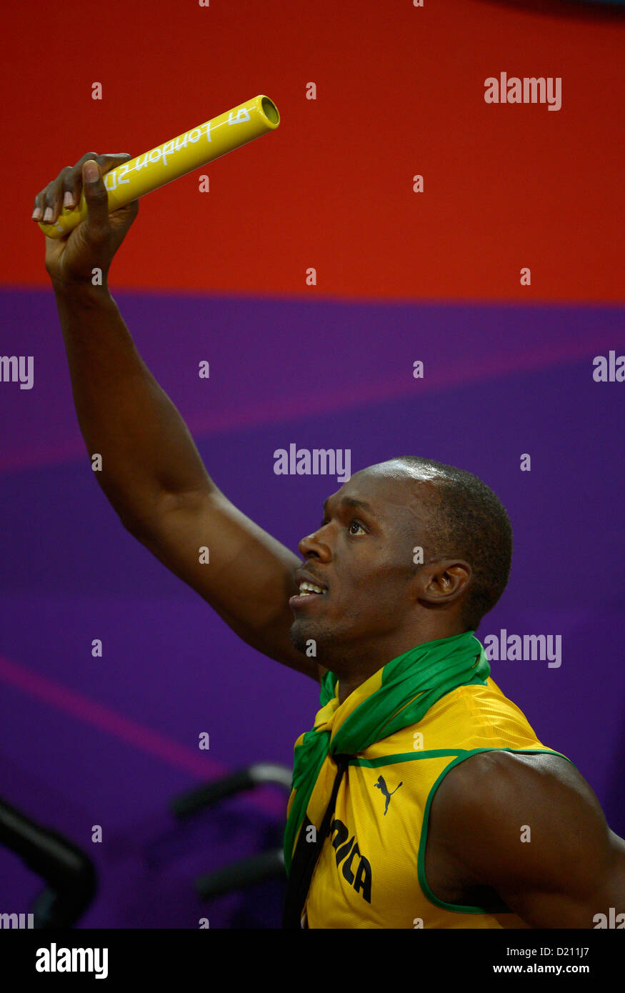 Jamaica's Usain Bolt is given the baton by officials after an earlier altercation. Athletics - Stock Image