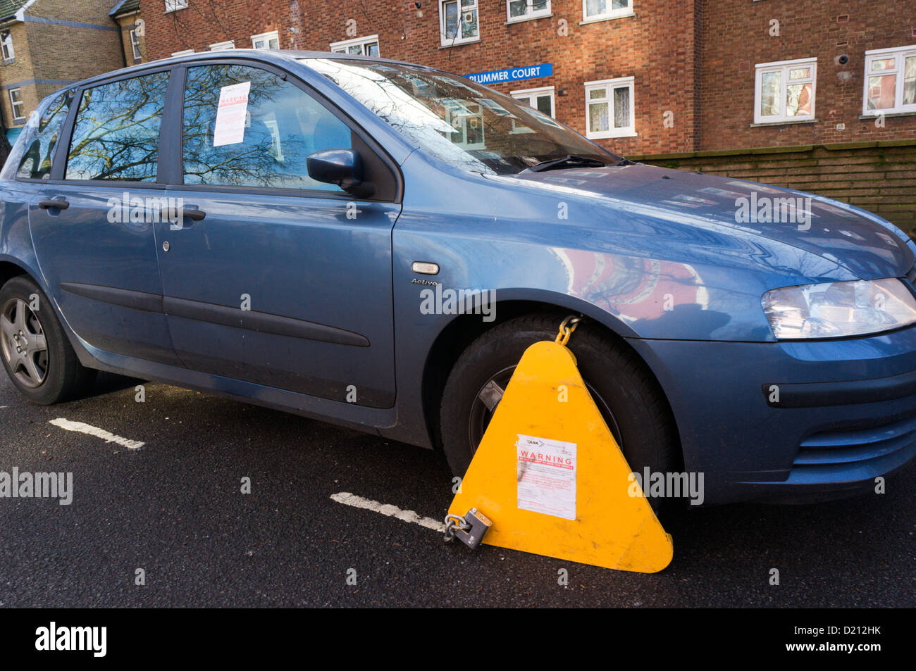 An illegally parked car that has been wheel-clamped. - Stock Image