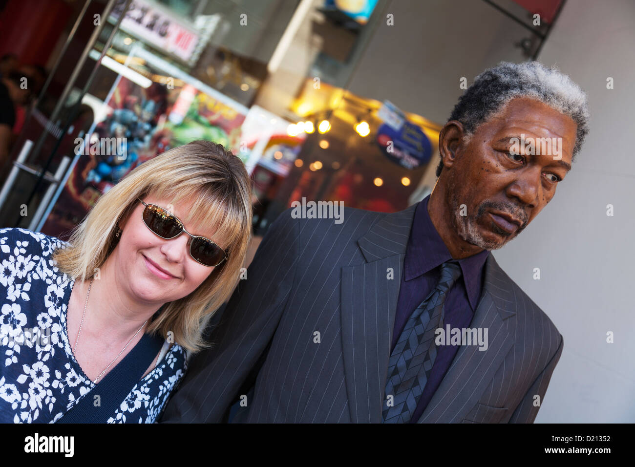 Pretty lady with wax work of Morgan Freeman outside Madame Tussauds