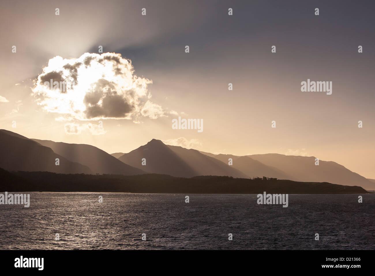 Backlit cloud and Beagle Channel coastline at sunset seen from cruise ship MS Deutschland (Reederei Peter Deilmann), - Stock Image