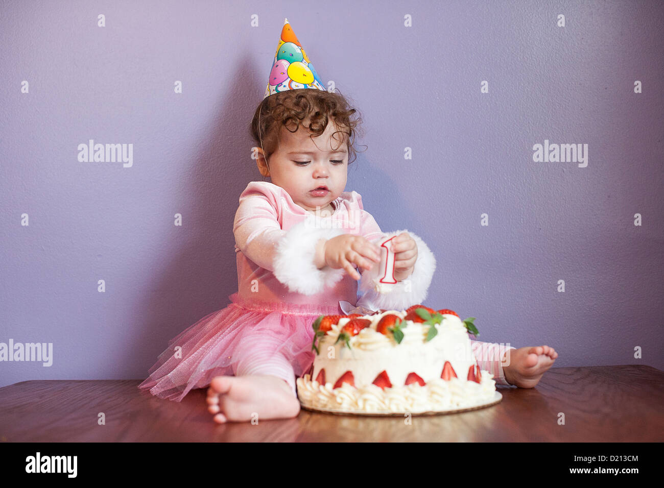cute baby girl wearing a party hat, eating and playing with a stock