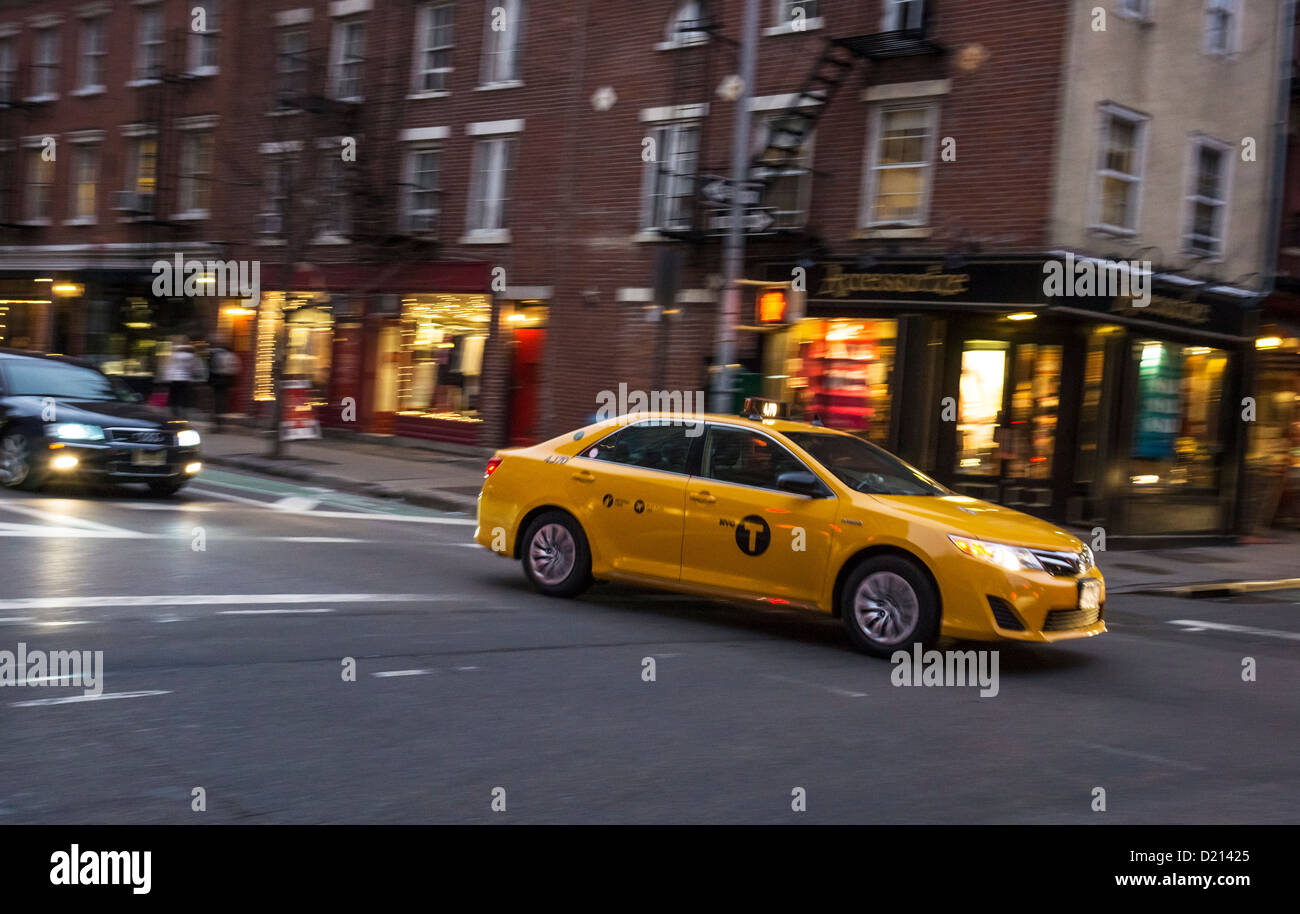 A hybrid yellow taxicab at night in New York City Stock Photo