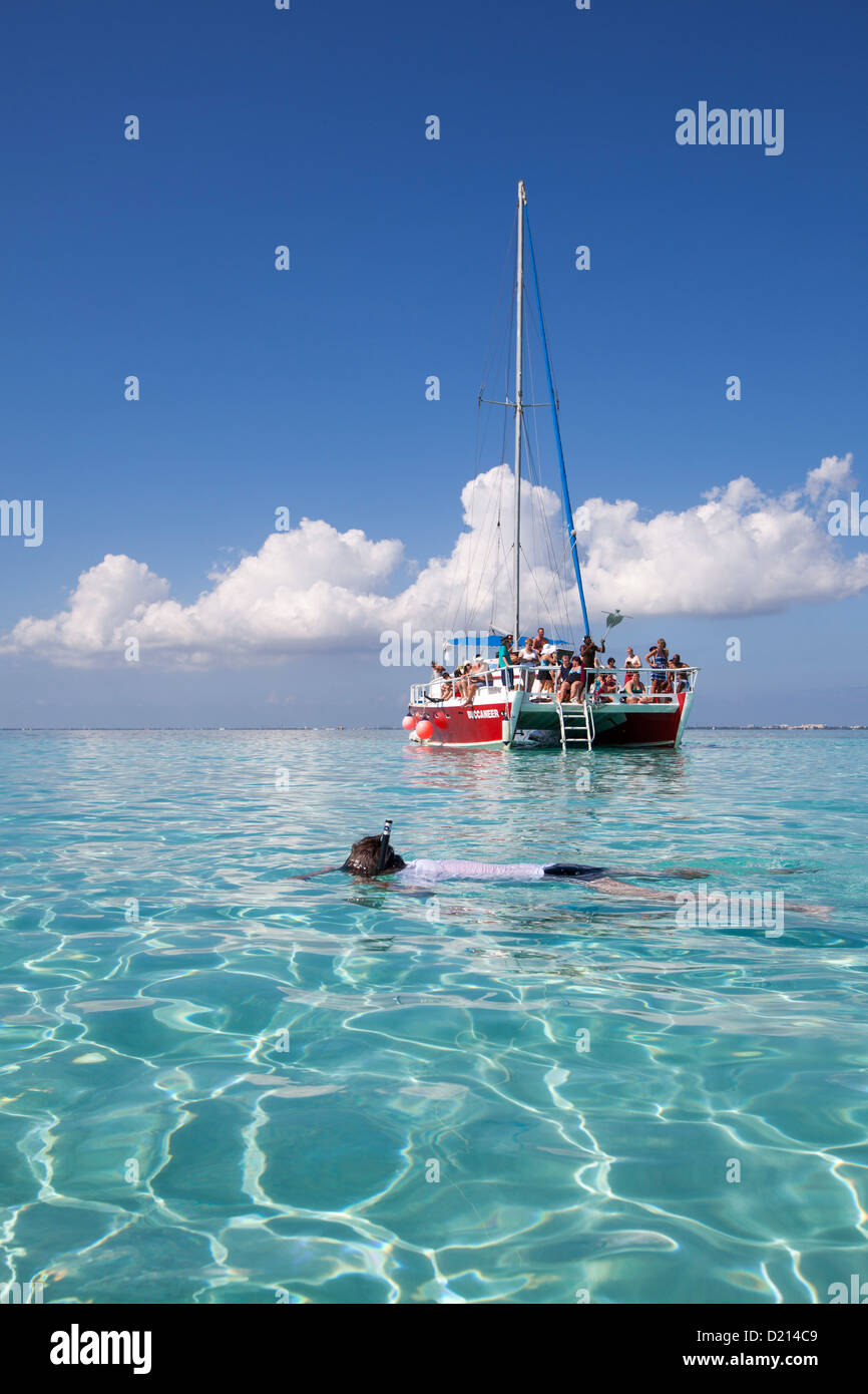Snorkeler and catamaran sailboat at Stingray City sand bank, Grand Cayman, Cayman Islands, Caribbean - Stock Image
