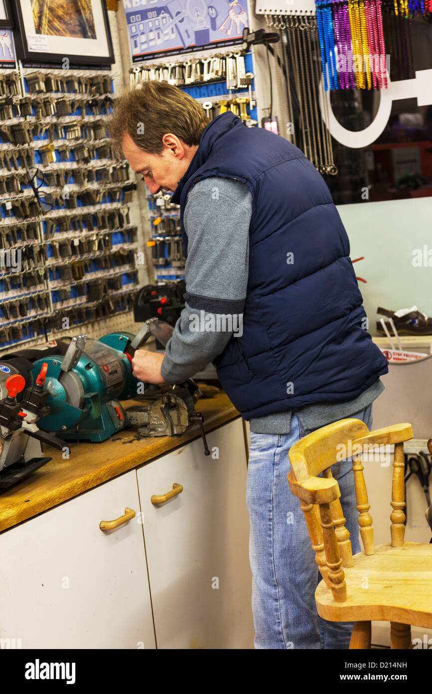 Man cutting keys in locksmith shop UK key cut and copied - Stock Image