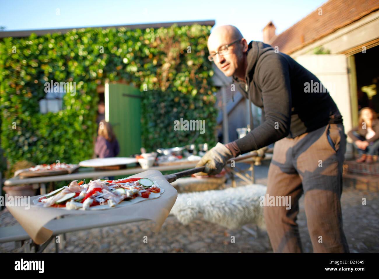 Man with pizza on a bread shovel, Klein Thurow, Roggendorf, Mecklenburg-Western Pomerania, Germany - Stock Image