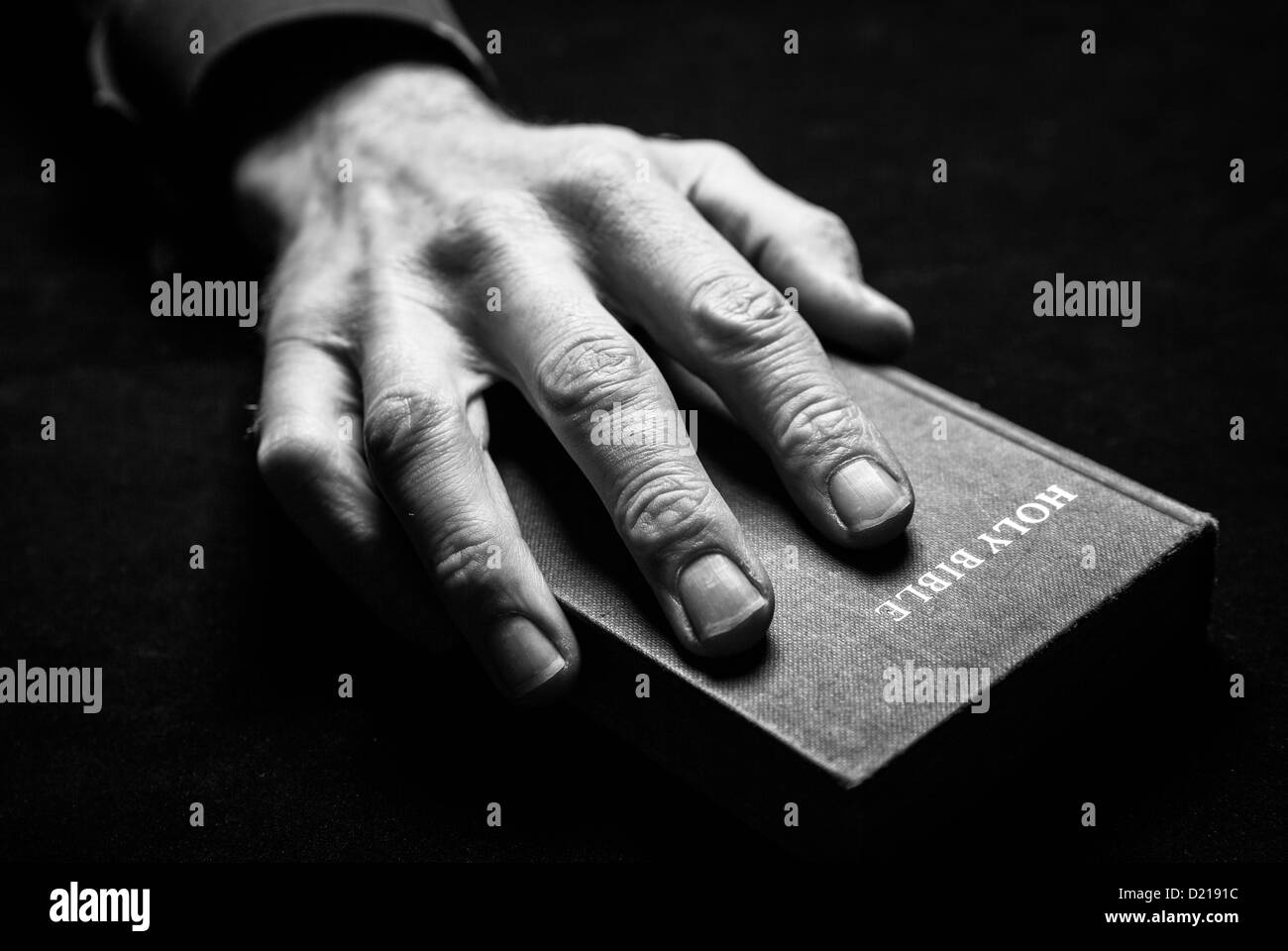 A black and white image of a mans hand holding the Holy Bible. - Stock Image