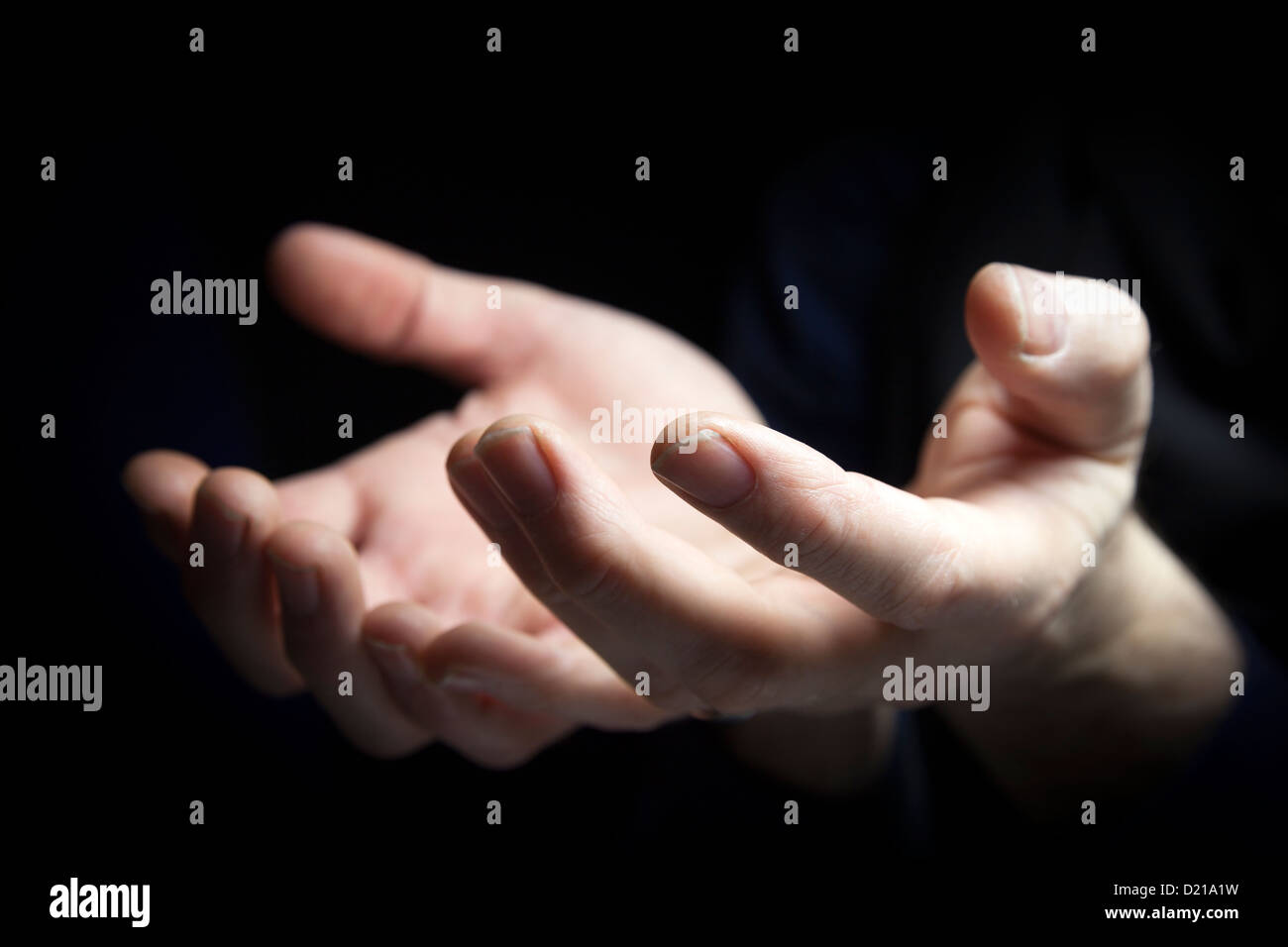 Two hands outstretched begging. - Stock Image