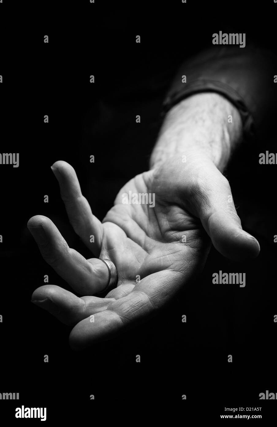 A hand reaching out to help someone. - Stock Image