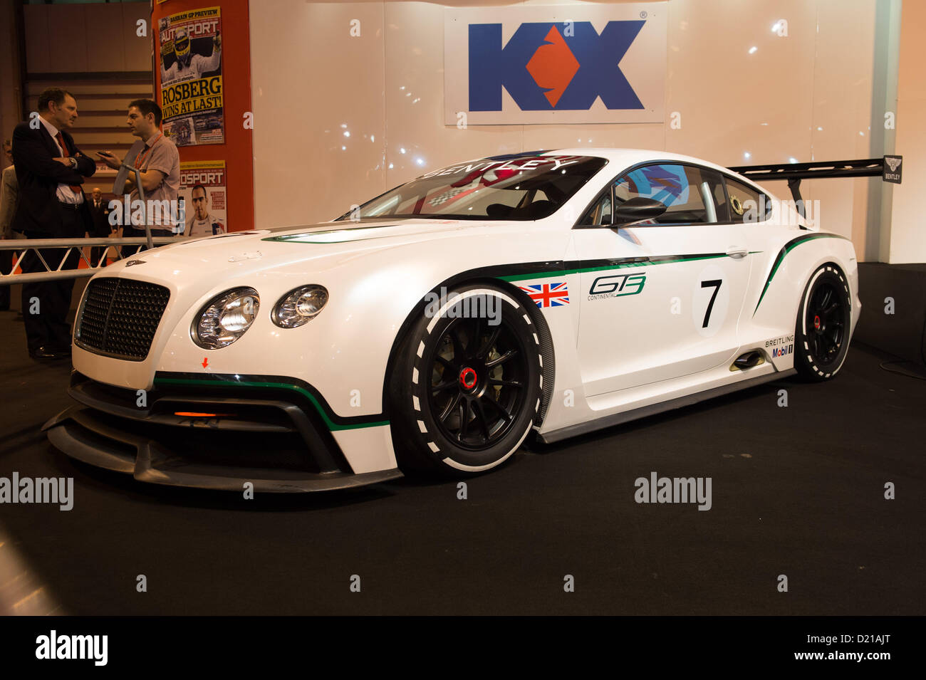 The new Bentley Continental GT3 car with Brian Gush  of Bentley being interviewed in the background at Autosport - Stock Image