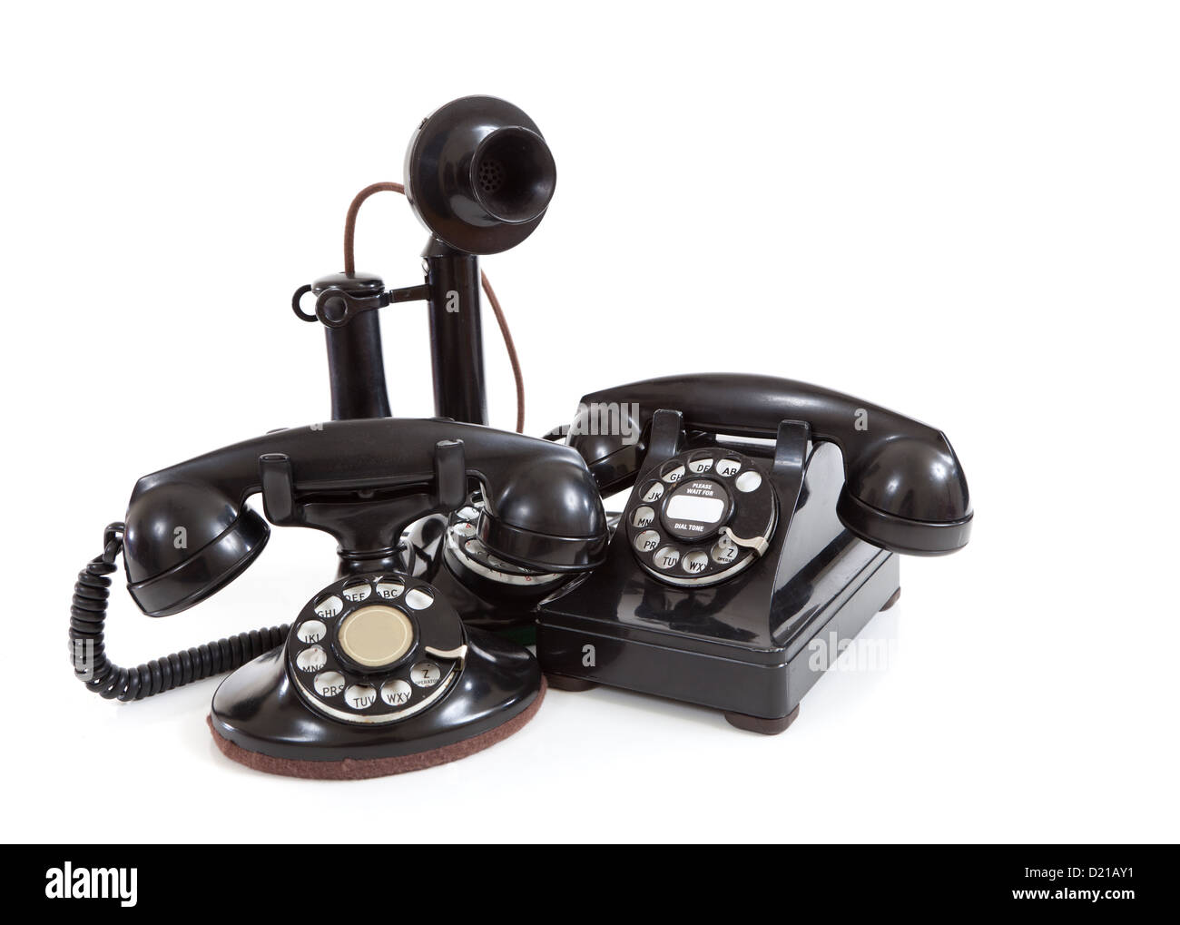 A group of vintage telephones on a white background - Stock Image