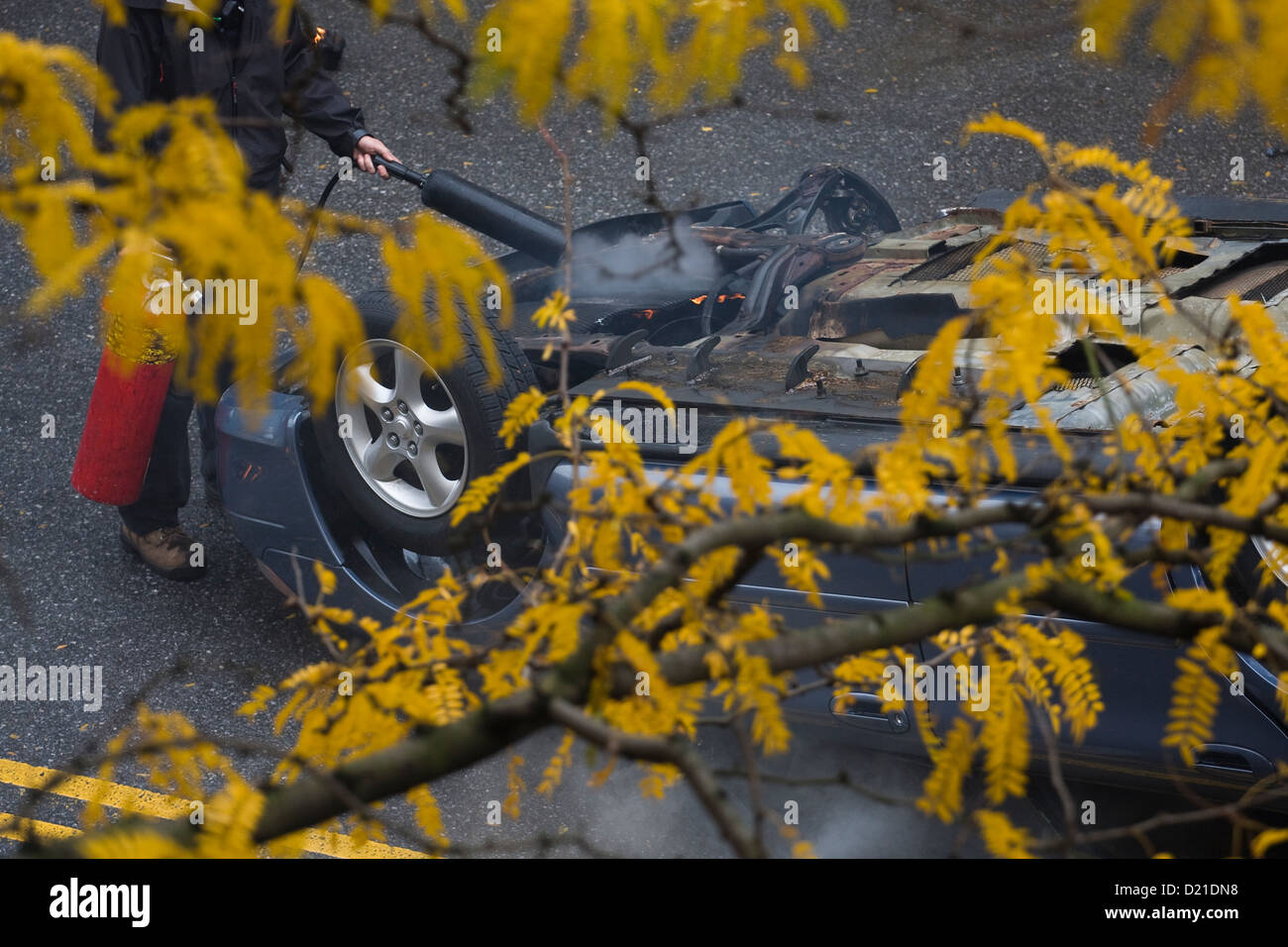 A man using a red fire extinguisher to put out a fire on an overturned automobile on a street - Stock Image