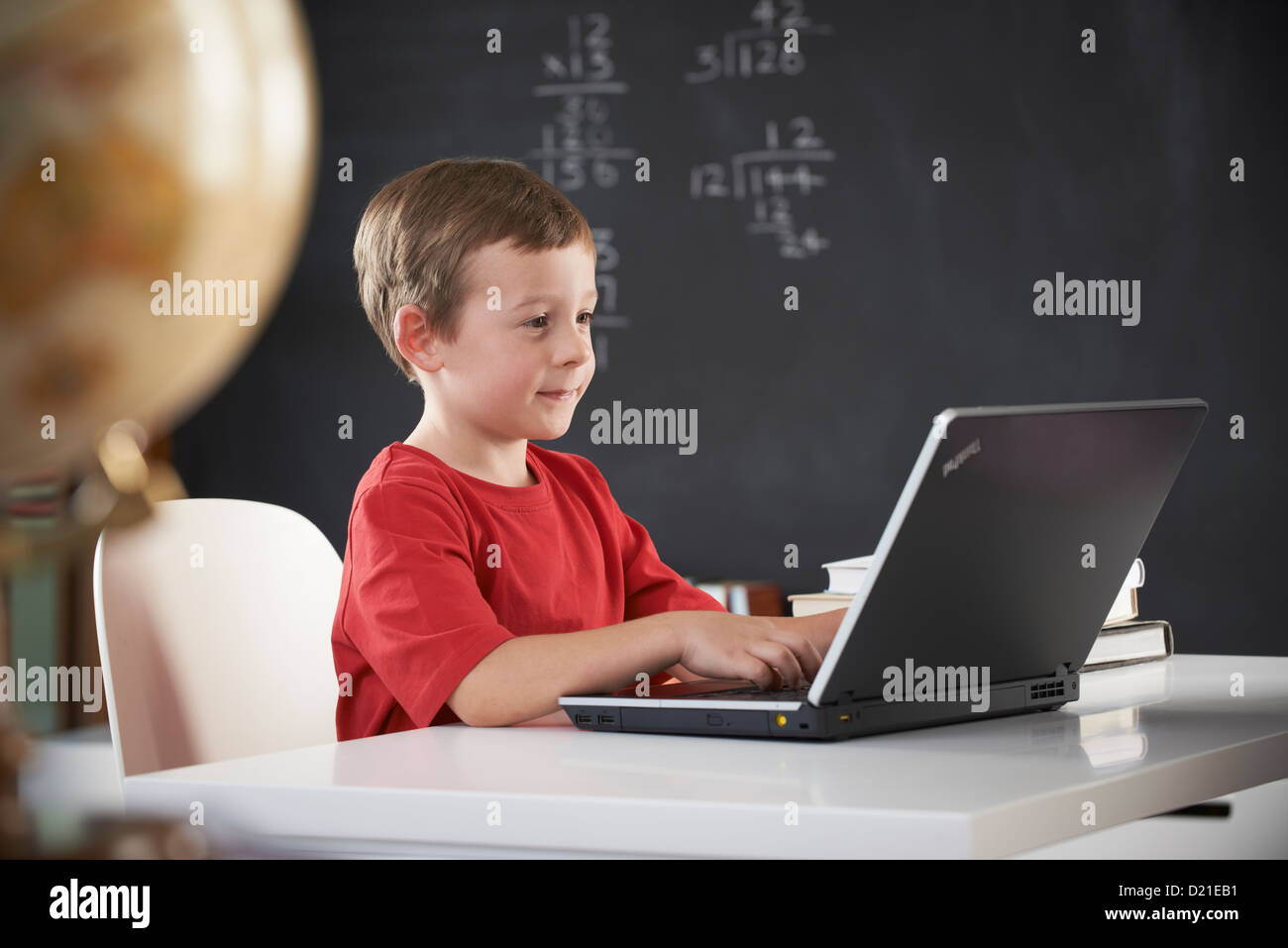 Young boy working on computer at school - Stock Image