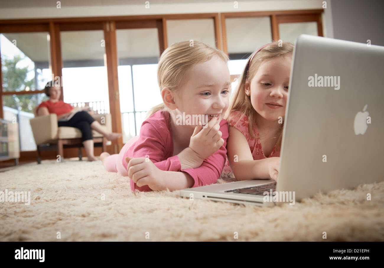 Young girls at home using laptop - Stock Image