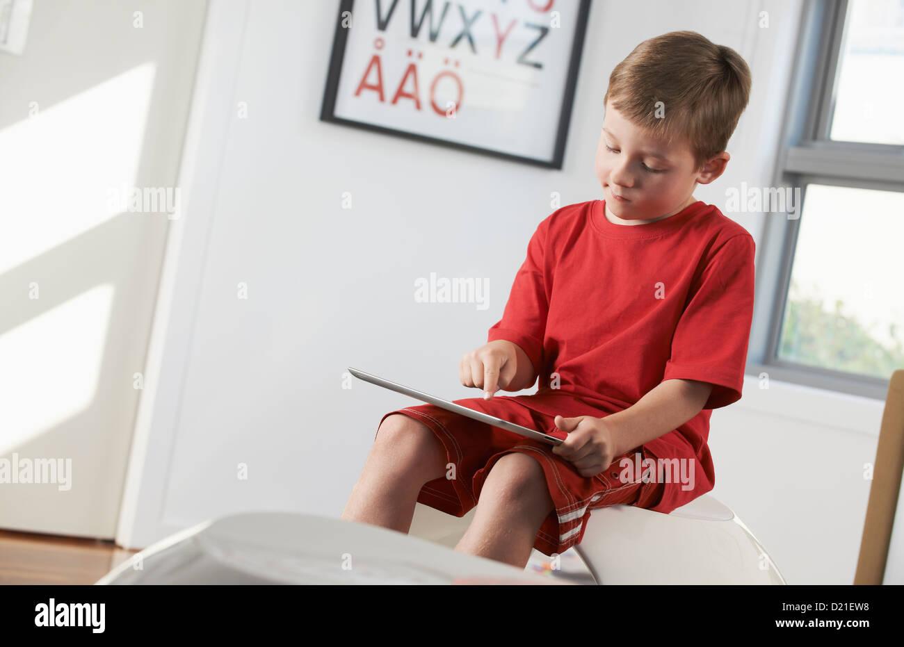Young boy using ipad at home - Stock Image