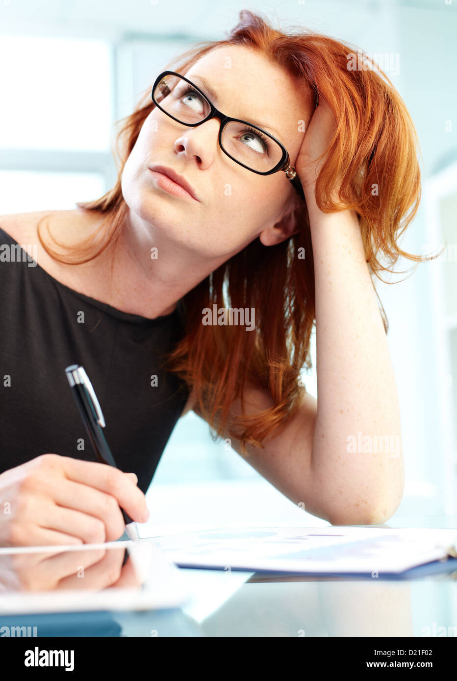 Vertical shot of a woman being deep in thought - Stock Image