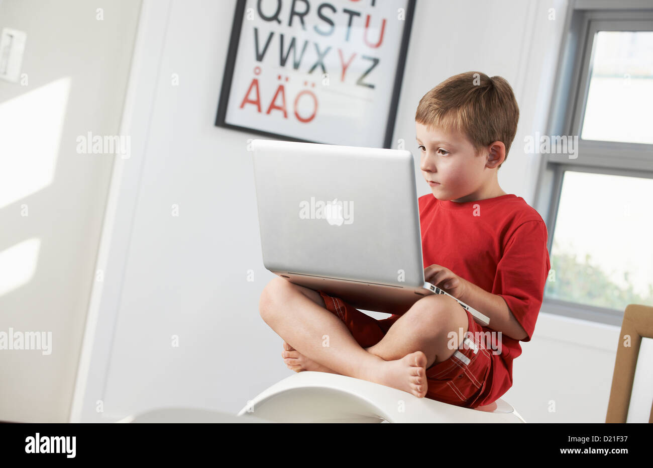 Young boy using laptop at home - Stock Image