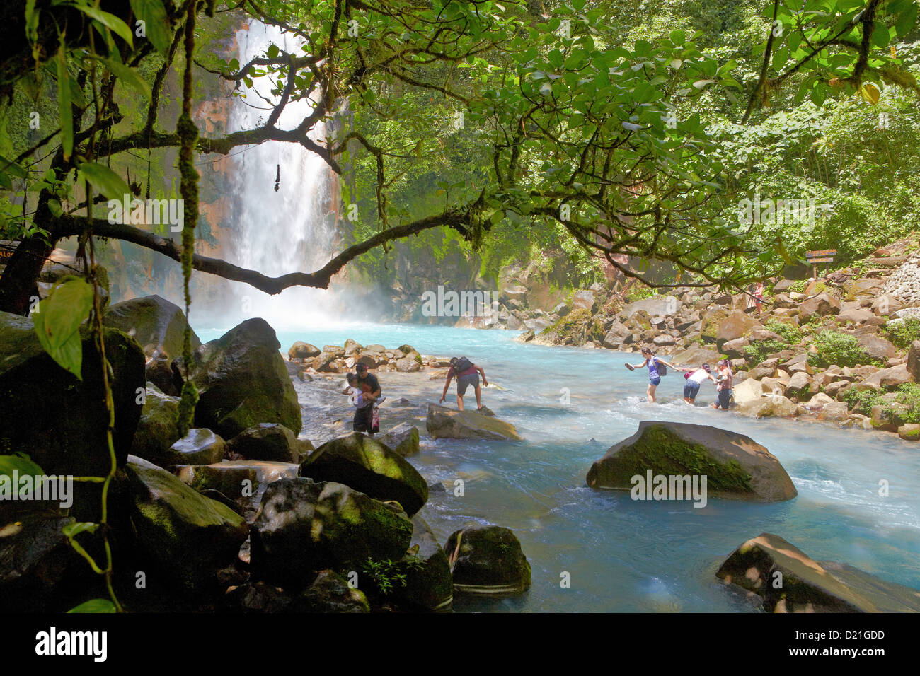 People in front of waterfall Rio Celeste at Tenorio National Park, Costa Rica, Central America, America - Stock Image
