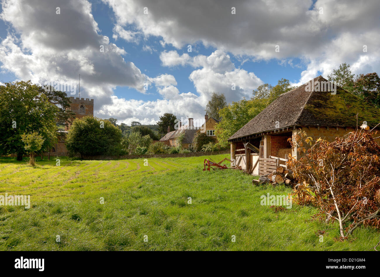 English village scene with church, cottages and barn - Stock Image