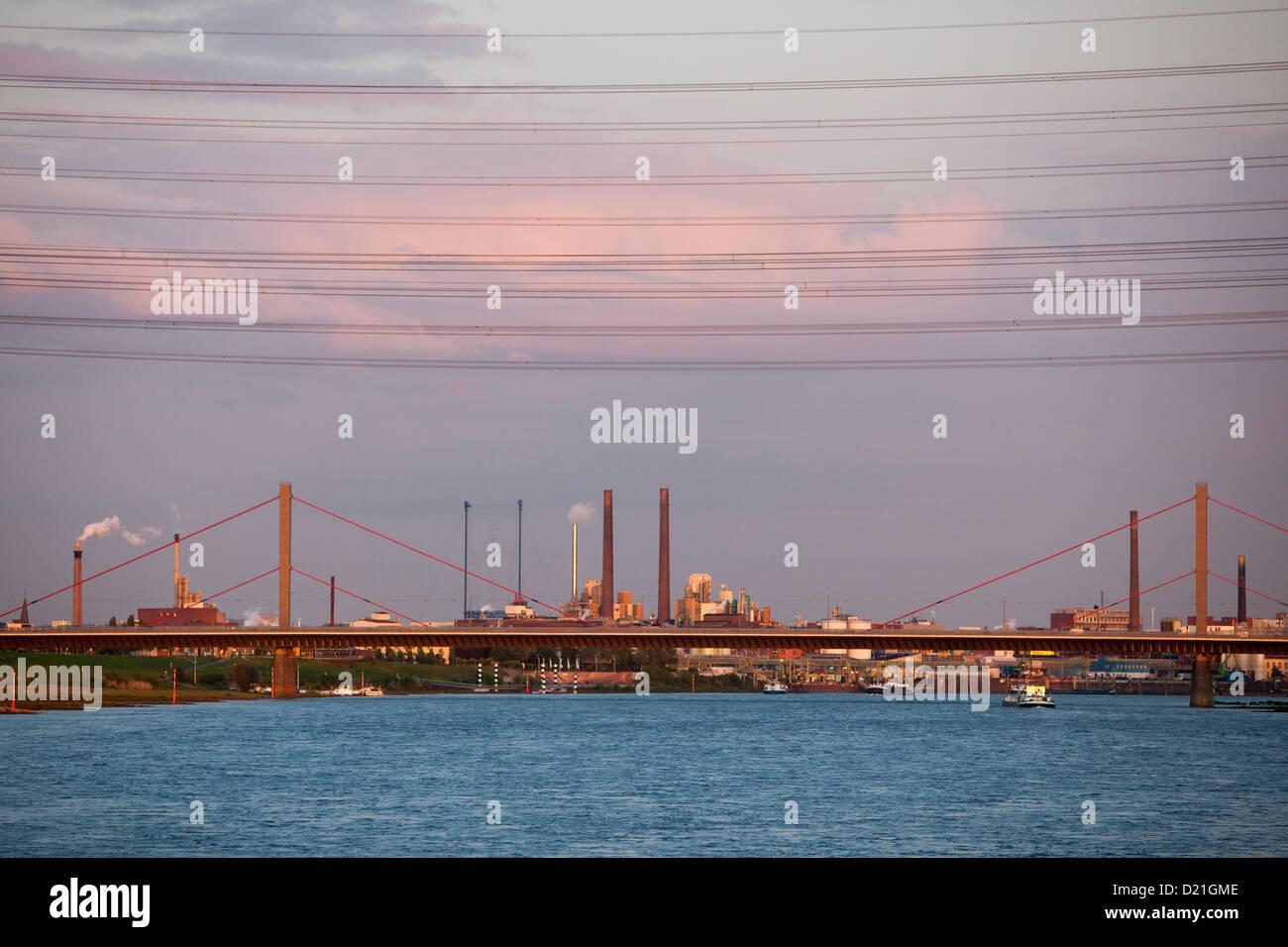 Rhine river and Bayer chemical and pharmaceutical company factory chimneys at dusk, Leverkusen, North Rhine-Westphalia, - Stock Image