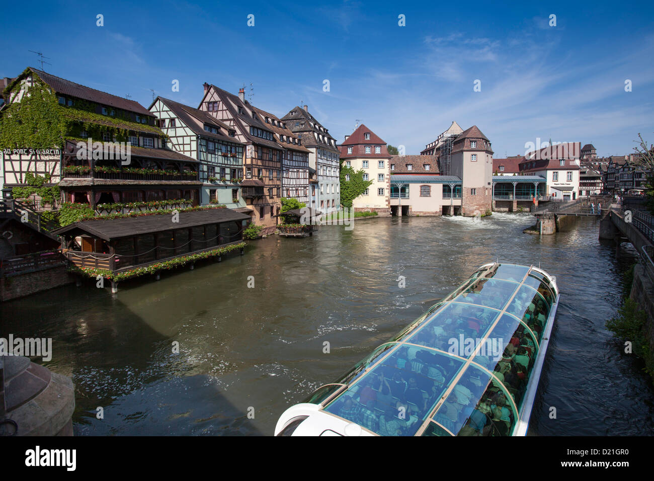 Restaurant Au Pont St. Martin and half-timbered houses and sightseeing boat on canal in La Petite France district, - Stock Image