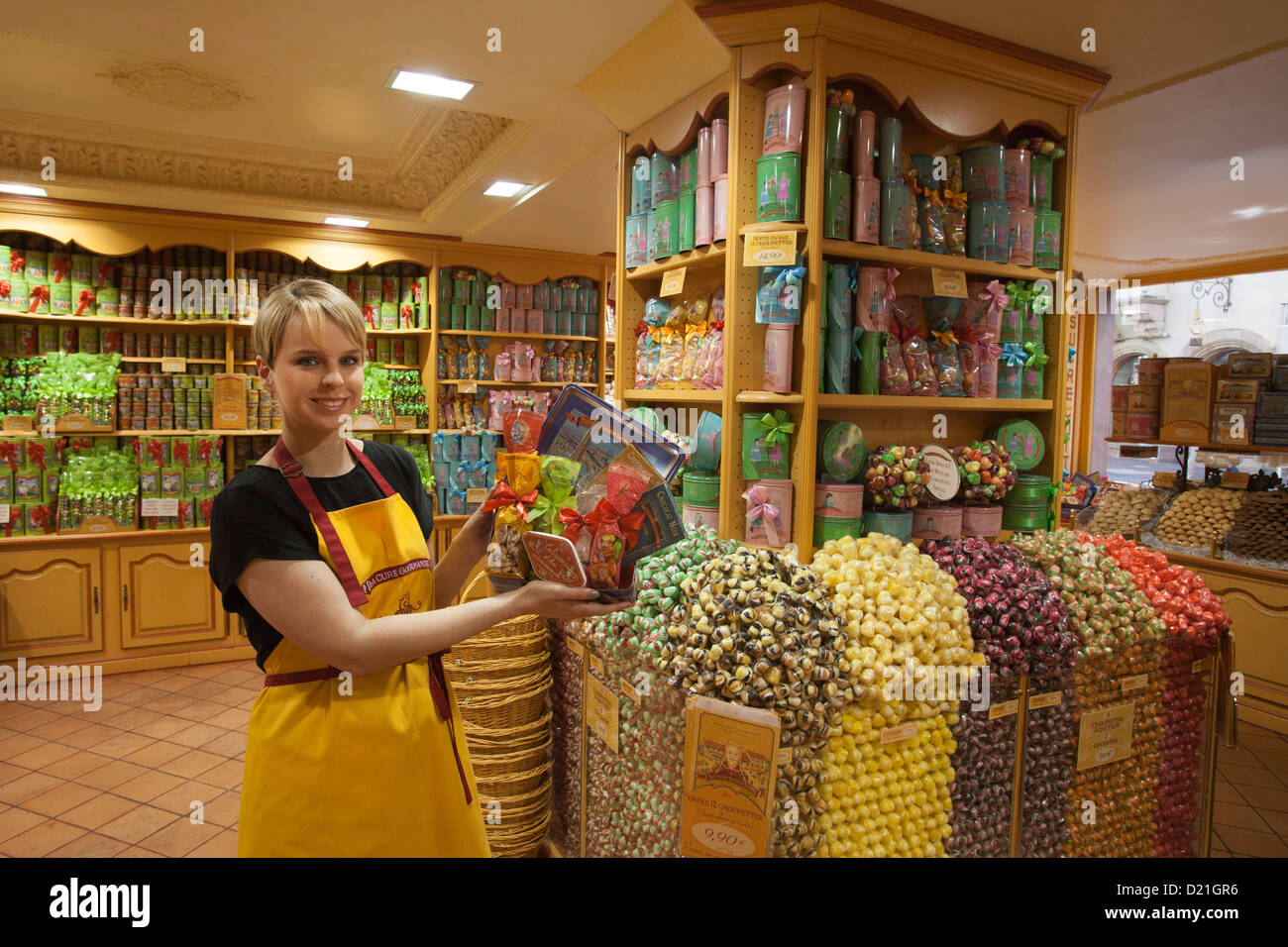 Salesgirl showing sweets for sale at La Cure Gourmande Biscuitier Sucrecuitier candy shop, Strasbourg, Alsace, France, - Stock Image